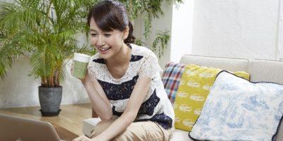 コーヒーを飲みながらPCを見る女性
