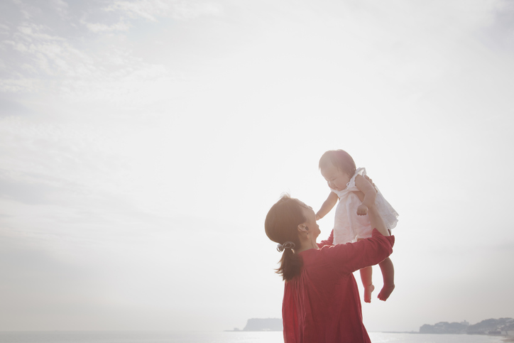 Asian mother holding her daughter at seaside.